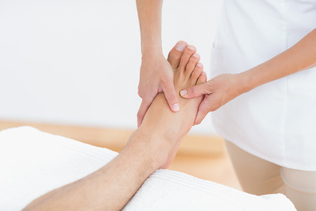 Physiotherapist doing foot massage in medical office photo