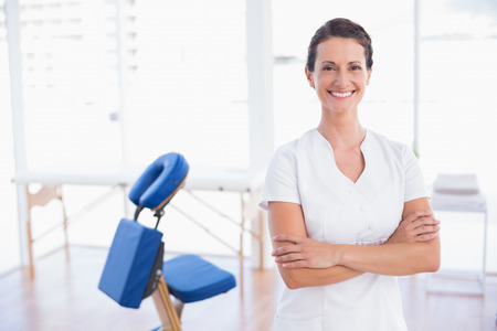 Smiling therapist standing with arms crossed in medical office Stockfoto