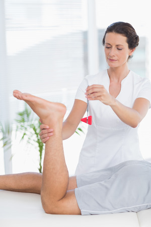 achilles tendon: Physiotherapist using reflex hammer in medical office Stock Photo