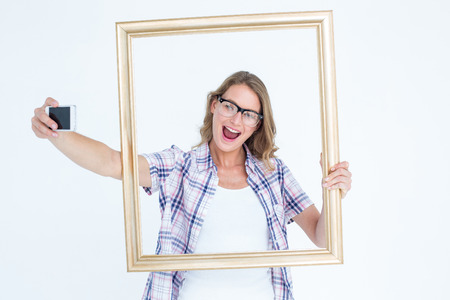 geeky: Pretty geeky hipster taking selfie with smartphone on white background