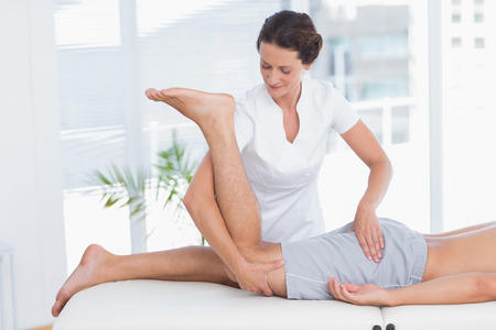 Physiotherapist doing leg massage to her patient in medical office photo