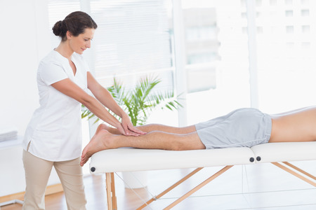 Physiotherapist doing calf massage to her patient in medical office photo