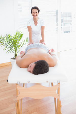 massage  table: Patient relaxing on the massage table with physiotherapist behind in medical office