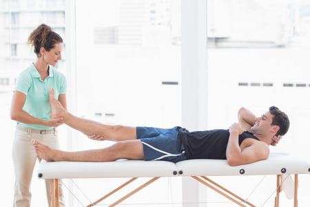 physiotherapy: Doctor examining man leg in medical office