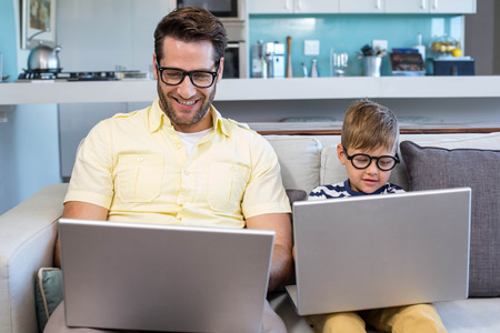 Father and son using laptops on the couch at home in the living room Stock Photo
