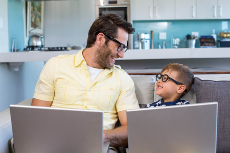 father: Father and son using laptops on the couch at home in the living room Stock Photo