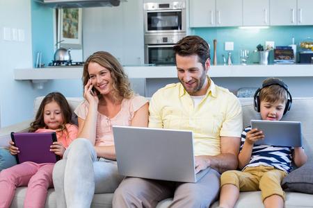 自宅のデバイスを使用して、リビング ルームのソファの上幸せな家族