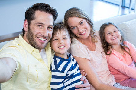 Happy family taking selfie on couch at home in the living room photo