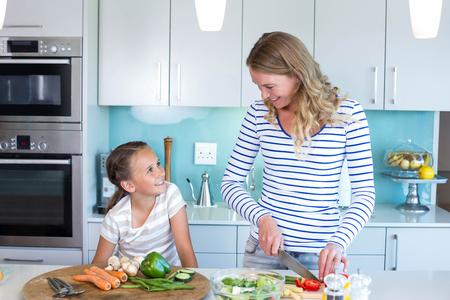 幸せな家族の自宅台所で一緒に昼食を準備