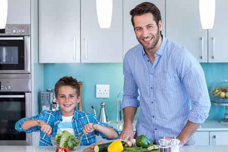 one mid adult male: Happy family preparing lunch together at home in the kitchen Stock Photo