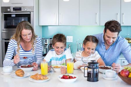 niños desayunando: La familia feliz desayunando juntos en casa en la cocina