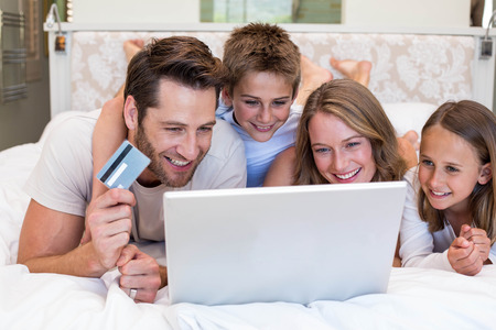 Happy family on the bed using laptop at home in bedroom photo