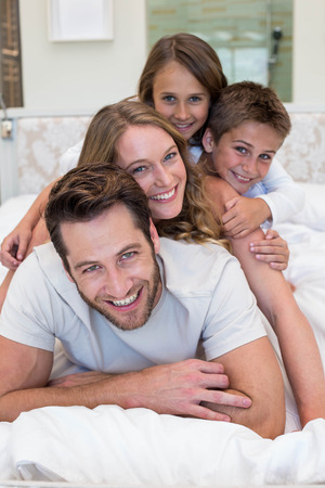 Happy family on the bed at home in bedroom