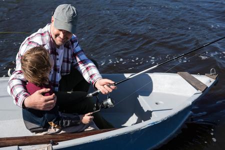 barca da pesca: Pesca uomo felice con suo figlio in barca Archivio Fotografico