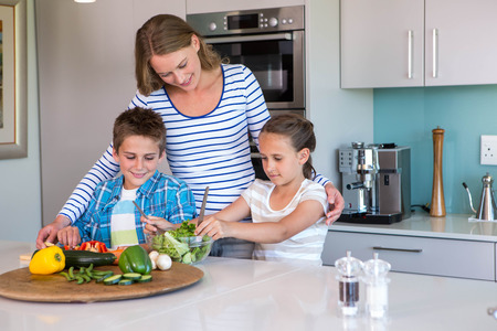 Happy family preparing lunch together at home in the kitchen photo