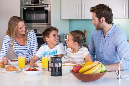 Gelukkige familie samen ontbijten thuis in de keuken