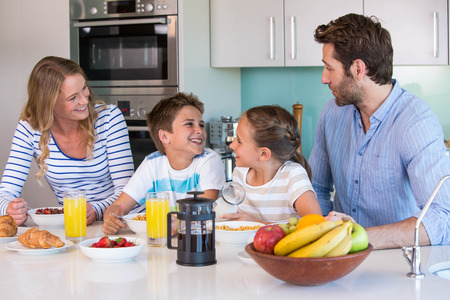 Happy family having breakfast together at home in the kitchen