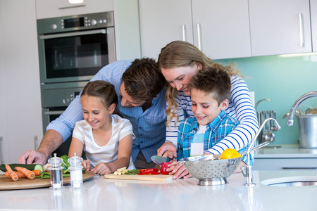 niños sanos: Familia feliz que se prepara verduras juntos en casa en la cocina