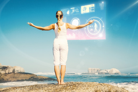 arms out: Blonde woman standing on beach on rock with arms out against fitness interface