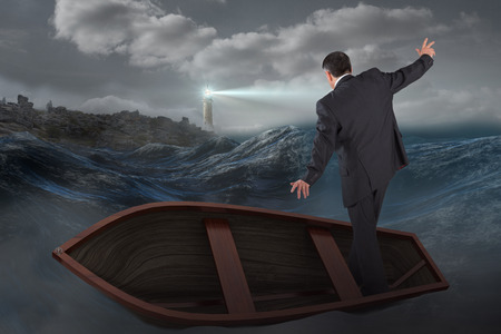 stormy sea: Businessman balancing in boat against stormy sea with lighthouse Stock Photo