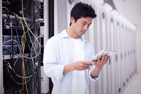 touch technology: Male looking at his tablet computer against data center Stock Photo