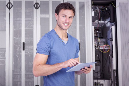 scrolling: Man scrolling through tablet pc against data center