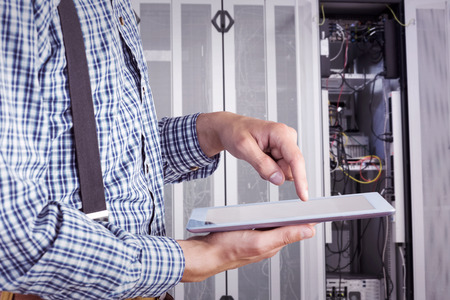 Geeky businessman using his tablet pc against data center photo