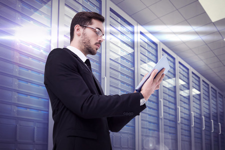 server room: Businessman with glasses using his tablet against server room