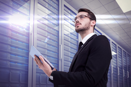 server hardware: Businessman looking away while using tablet against server room