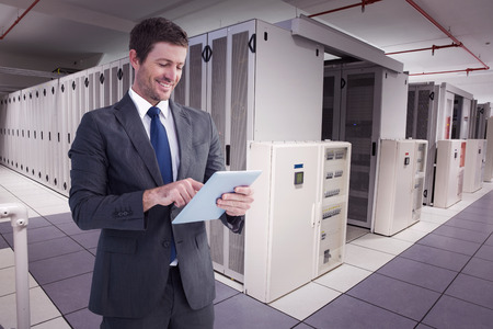 computer center: Hombre de negocios usando su PC de la tableta contra el centro de datos Foto de archivo