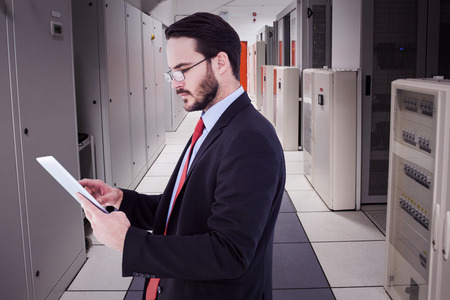 computer server: Businessman scrolling on his digital tablet against data center Stock Photo
