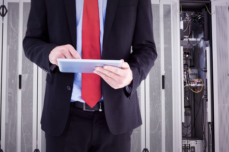 scrolling: Businessman scrolling on his digital tablet against data center Stock Photo