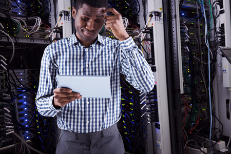 Young businessman thinking and holding tablet against data center photo