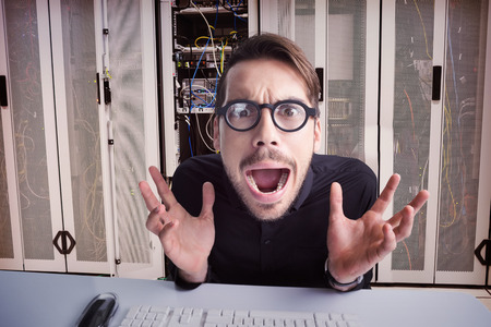 Worried businessman with glasses using computer  against data center