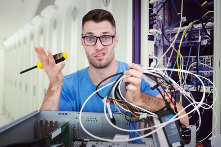 confundido: Retrato de confundida que profesional con un destornillador y los cables frente a la CPU abierta contra los centros de datos Foto de archivo