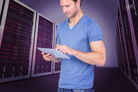 scrolling: Man scrolling through tablet pc against server hallway Stock Photo