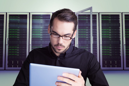 Cheerful businessman in glasses using tablet against server towers photo