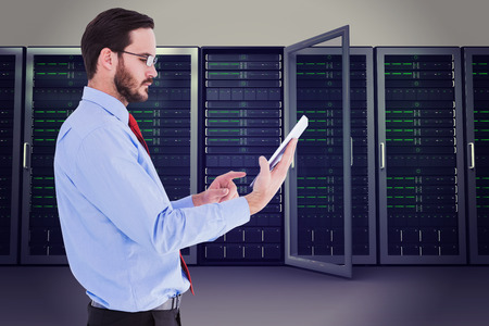 Businessman scrolling on his digital tablet against server towers photo
