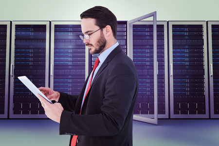 scrolling: Businessman scrolling on his digital tablet against server towers Stock Photo