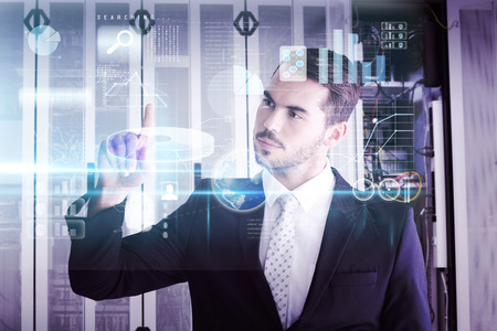 Thoughtful businessman pointing something with his finger against data center Stock Photo