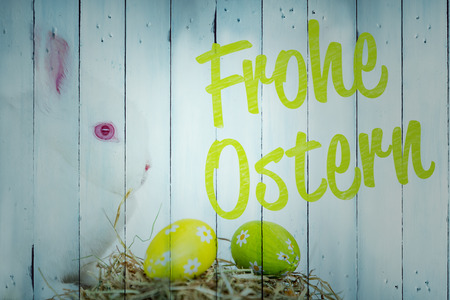 Ostern: frohe ostern against white bunny beside nest of foil wrapped easter eggs