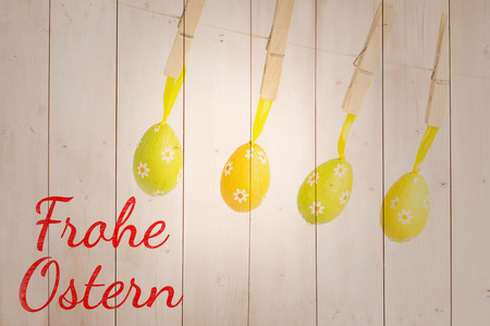 Ostern: frohe ostern against four easter eggs hanging from a line Stock Photo