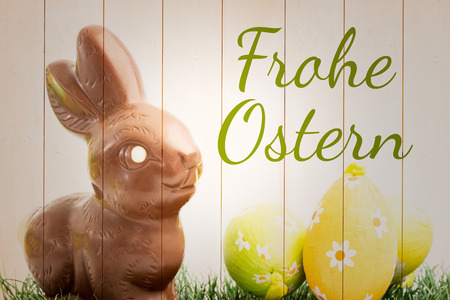 Ostern: frohe ostern against chocolate bunny rabbit and three easter eggs