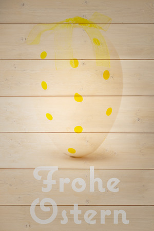 frohe: frohe ostern against yellow easter egg with ribbon