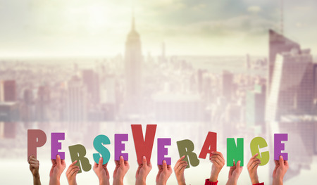 perseverance: Hands showing perseverance against room with large window looking on city Stock Photo