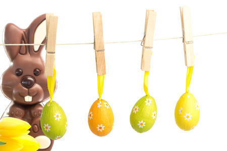 easter sunday: hanging easter eggs against yellow tulips with cute chocolate bunny