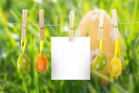 nestled: hanging easter eggs against easter egg nestled in the grass