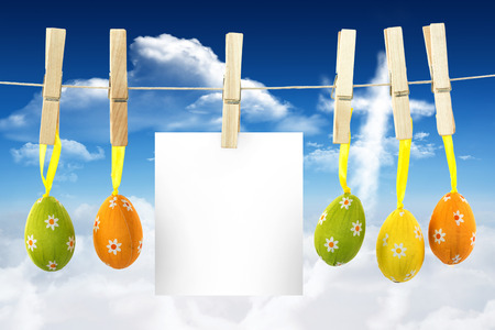 hanging easter eggs against cross shape in the sky photo