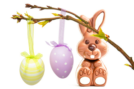 Hanging easter eggs against cute chocolate bunny