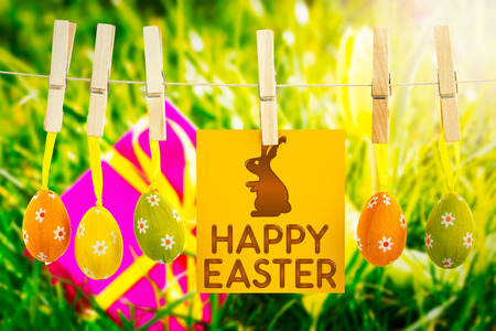 happy easter graphic against pink gift with easter egg and yellow tulip photo